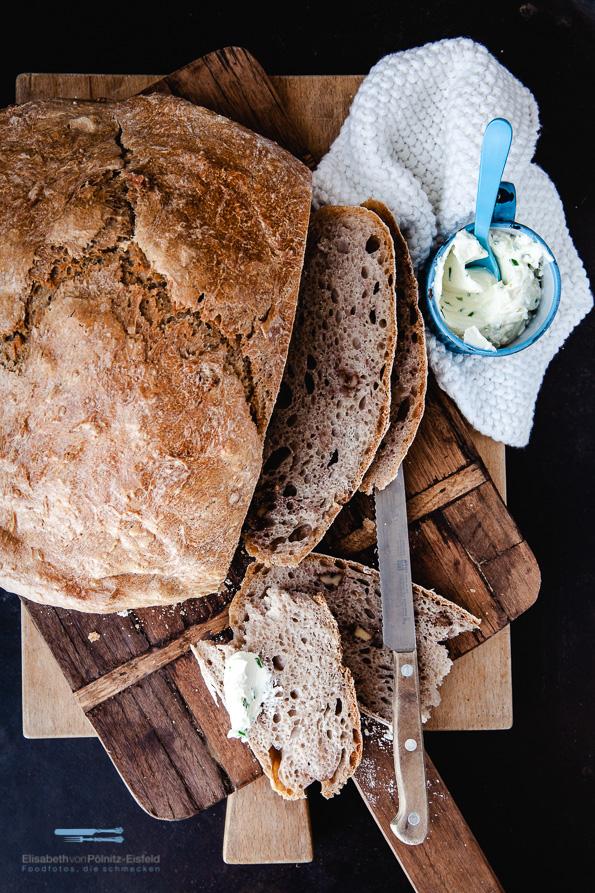 Aufgeschnittenes Brot auf zwei Holzbrettchen dazu einen Tasse mit Kräuterfrischkäse