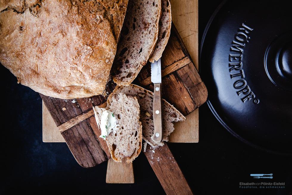 Aufgeschnittenes Brot Neben Dem Deckel Des Römertopf Schmortopfs.