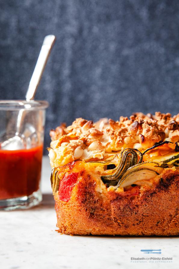 Kuchen, angeschnitten mit Zucchini und Tomaten.